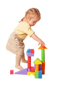 Baby girl building from toy blocks. Isolated on white background